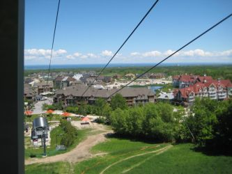 View of Blue Mountain Village from summer gondola: Taken from the summer gondola ride which takes you up Blue Mountain for great panoramic views and access to Scenic Caves. This is a view down towards the village with Nottawasaga Bay (Part of Georgian Bay) in the background, towards the town of Collingwood and Wasaga Beach. The same gondola takes mountain bikes and bikers to the top.