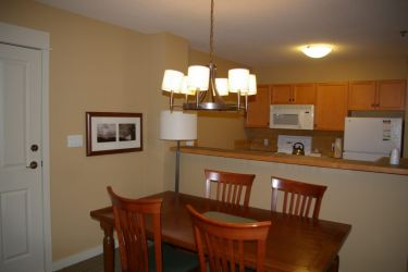 Dining Room/Kitchen in 1-3 bedroom unit: An example of Dining area and full Kitchen behind a breakfast bar which you will see in a 1, 2, or 3 bedroom full-size unit.